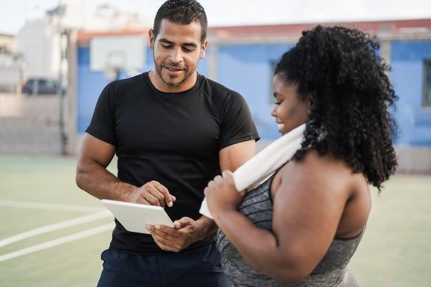 Bochtige vrouw praten met haar persoonlijke trainer tijdens het controleren van tech klembord buiten