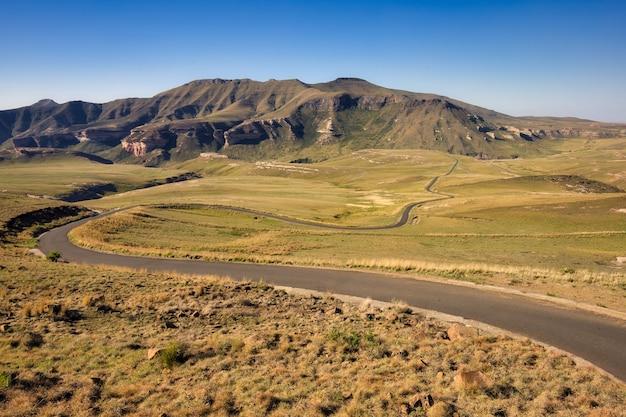Bochtige weg in het midden van grasvelden met bergen in de verte in de provincie oost-kaap