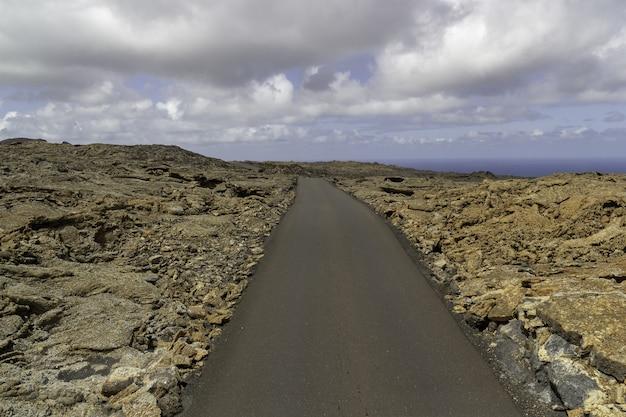 Bochtige weg omgeven door rotsen onder een bewolkte hemel in het timanfaya national park in spanje