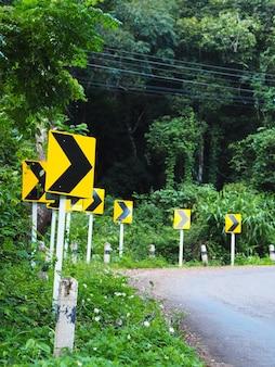 Bochtwaarschuwingsbord op kronkelende weg in het bos om voorzichtig te rijden.