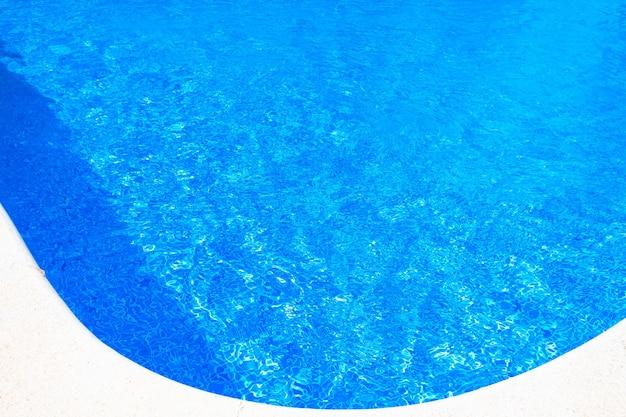 Bodem van een zwembad met kleine blauwe tegels gezien door het verfrissende water in de zomer.