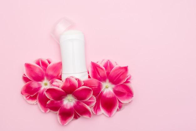 Body anti-transpirant deodorant met bloemen op roze oppervlak