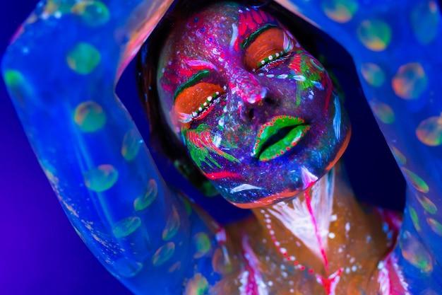 Body art gloeit in ultraviolet licht. body art op het lichaam en de hand van een meisje dat gloeit in het ultraviolette licht