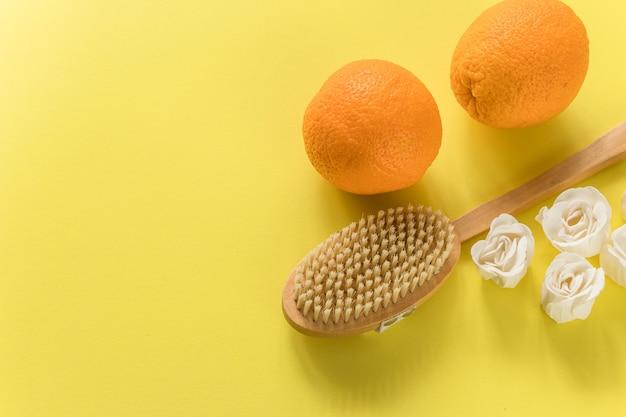 Body brush met grote sinaasappels en witte zeep in roosvorm voor anti-cellulitis massage op gele muur. plat ontwerp met kopie ruimte. cactus exfoliërende borstel voor lichaamsverzorging