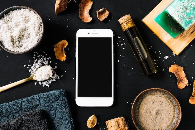 Body scrub; gedroogde schelp; essentiële olie; stuk zeep; servet en smartphone op zwarte achtergrond