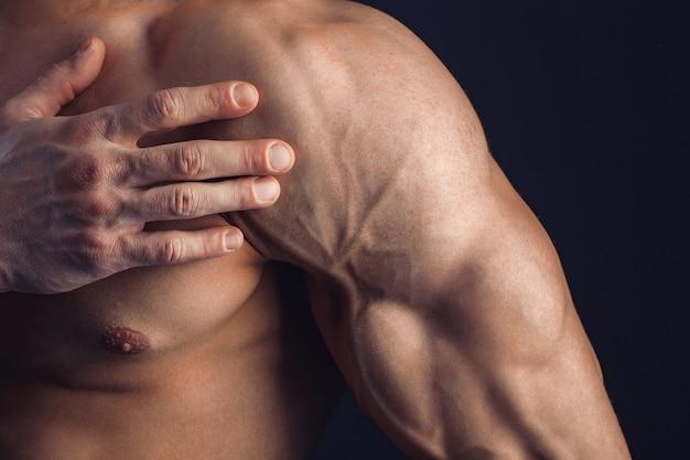 Bodybuilder die aan schouderpijn op donkere ruimte lijdt