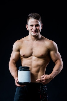 Bodybuilder die een zwart plastic weiproteïne van het kruik leeg wit etiket houden en naar het met zijn hand richten die op donkere muur wordt geïsoleerd