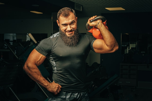 Bodybuilder die oefeningen met domoren in een donkere gymnastiek doen