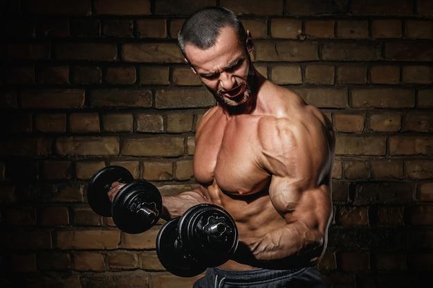 Bodybuilder die oefeningen voor bicepsen met domoren doen