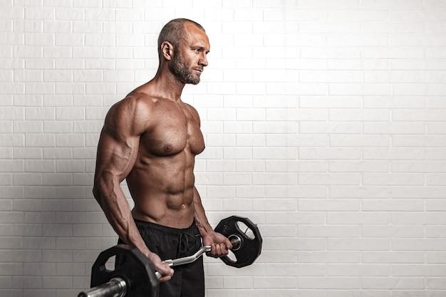 Bodybuilder doet oefeningen voor biceps met een halter tegen bakstenen muur.