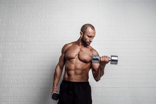 Bodybuilder doet oefeningen voor biceps met halters tegen bakstenen muur.