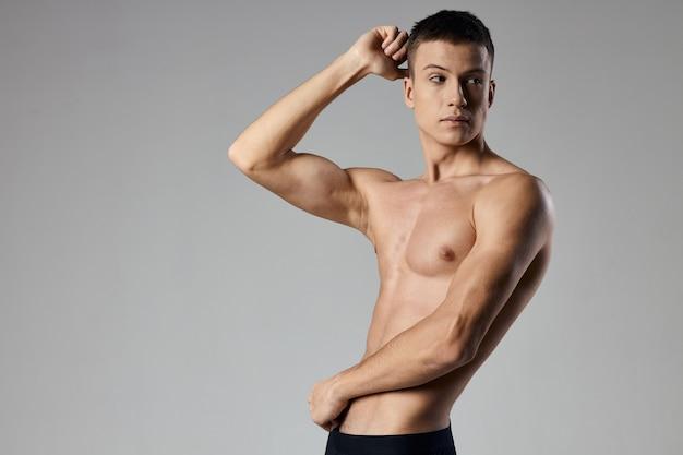Bodybuilder fitness man atleet op grijze achtergrond bijgesneden weergave kopie ruimte