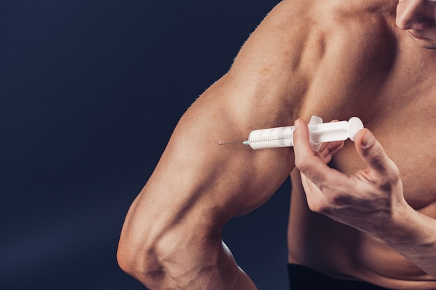 Bodybuilder injecteert vitamines. foto van sportieve man met perfecte lichaamsbouw op donkere achtergrond. kracht en motivatie