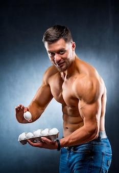 Bodybuilder jonge sportman houdt een verpakking met eieren, gezonde voedingseiwitten. camera kijken. naakte torso, gezond leven concept.