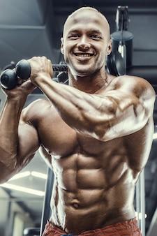 Bodybuilder knappe sterke atletische ruwe man oppompen van abs spieren training fitness en bodybuilding concept