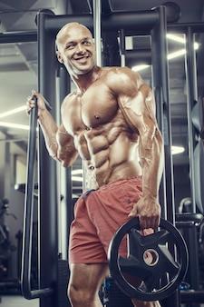 Bodybuilder knappe sterke atletische ruwe man oppompen van spieren training fitness en bodybuilding concept