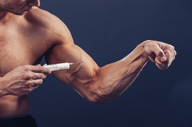 Bodybuilder maakt injectie van vitamines foto van sportieve man met perfecte lichaamsbouw op donkere achtergrond
