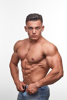 Bodybuilder man met perfecte buikspieren, schouders, biceps, triceps en borst, persoonlijke fitnesstrainer.