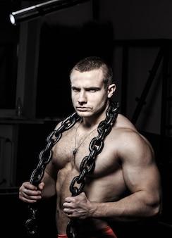 Bodybuilder met een ketting om zijn nek op een zwarte achtergrond