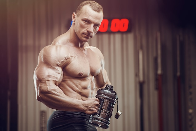 Bodybuilder met eiwitpoeder supplementen pot