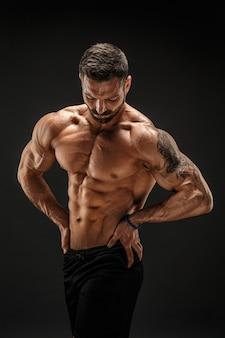 Bodybuilder poseren. fitness gespierde man op donkere muur.