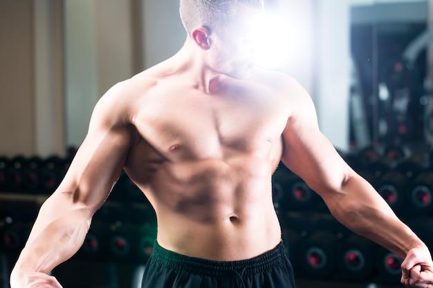 Bodybuilder poseren in de sportschool