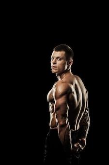 Bodybuilder poseren. mooie sportieve man mannelijke kracht. fitness gespierd lichaam. geïsoleerd op zwarte achtergrond