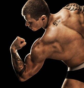 Bodybuilder poseren. mooie sportieve man mannelijke kracht. fitness mus
