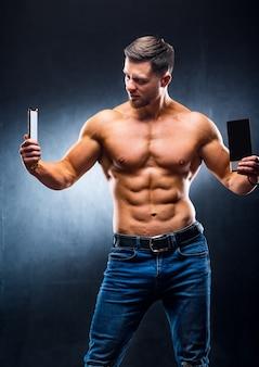 Bodybuilder sportman met sportreep en chocolade. kiezen tussen gezond en schadelijk voedsel. naakte torso. grijze achtergrond. verticale foto. detailopname