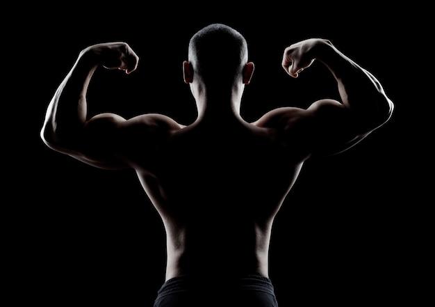 Bodybuilder toont biceps achteraanzicht op een donkere muur