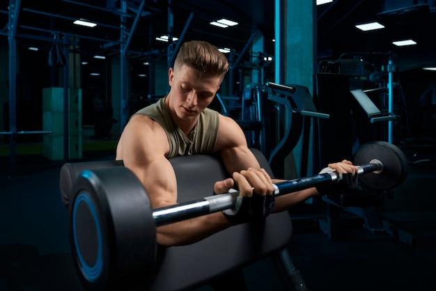Bodybuilder training biceps met barbell.