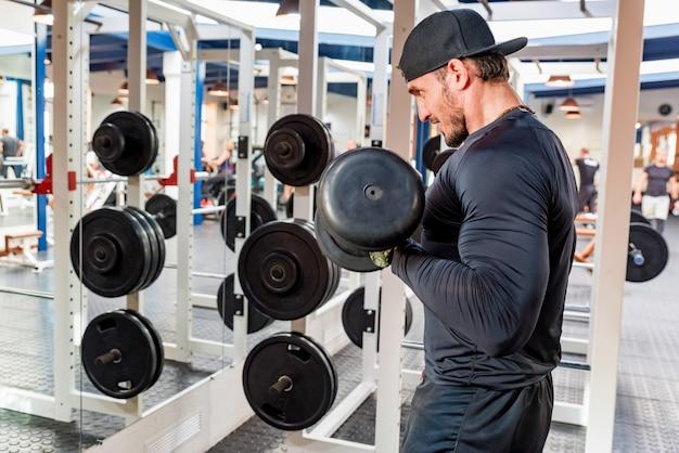 Bodybuilder traint biceps met dumbels. fitness en crossfit-concept. detailopname