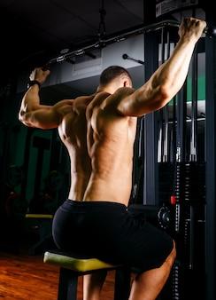 Bodybuilder van de machts de atletische kerel, voert oefening met gymnastiekapparatuur uit
