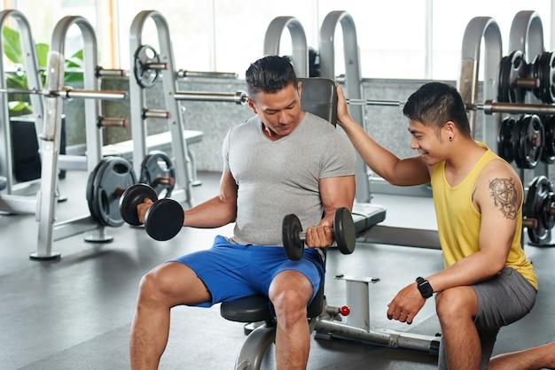Bodybuilder zittend op oefening bank opheffing halters gecontroleerd door persoonlijke bank