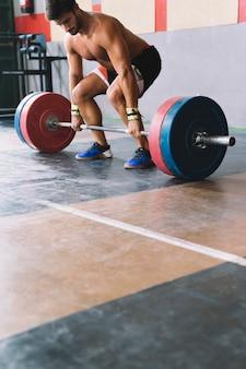 Bodybuilding concept met sterke man over het opheffen van barbell