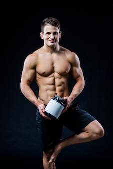 Bodybuilding en sport thema: knappe sterke bodybuilder met plastic pot met een droog eiwitgevoel ontspannen geïsoleerd in de studio