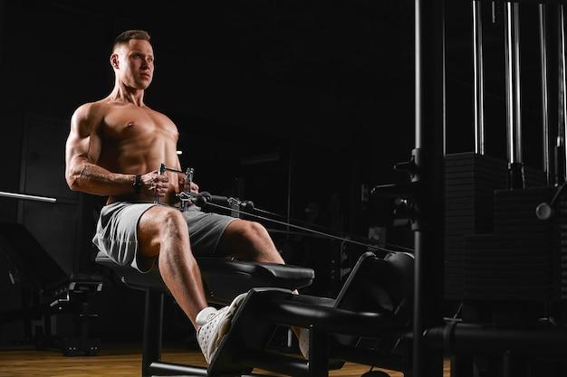 Bodybuilding, fitnessmotivatie, een mooi lichaam opbouwen, een man in de sportschool traint. fitnessmotivatie, positief lichaam.