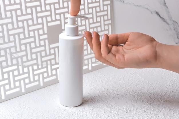 Bodylotion huidverzorging aanbrengen. vrouwen handen met body cream pompfles. schoonheid en lichaamsverzorging concept. natuurlijke schoonheid spa productconcept. mock-up dispenser
