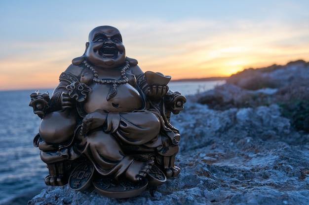 Boeddha-figuur op enkele rotsen, in de zonsondergang, op zee