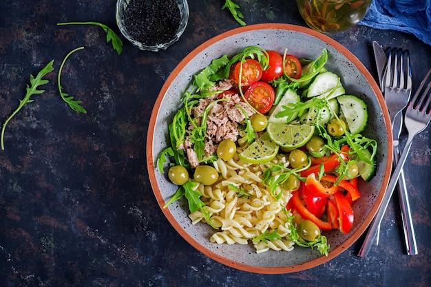 Boeddha schaal. pastasalade met tonijn, tomaten, olijven, komkommer, paprika en rucola op rustieke achtergrond