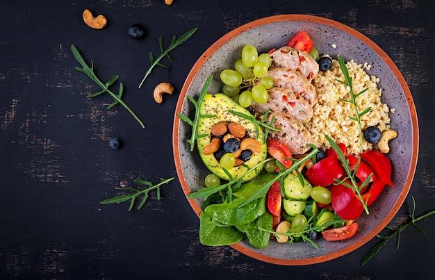 Boeddha schaaltje met gehaktbrood, bulgur, avocado, paprika, tomaat, komkommer, bessen en noten. detox en gezond superfoods komconcept. bovenaanzicht, platliggend