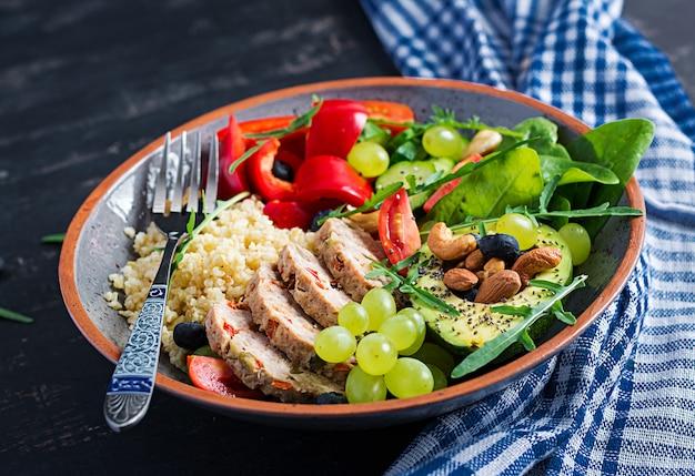 Boeddha schaaltje met gehaktbrood, bulgur, avocado, paprika, tomaat, komkommer, bessen en noten. detox en gezond superfoods komconcept.