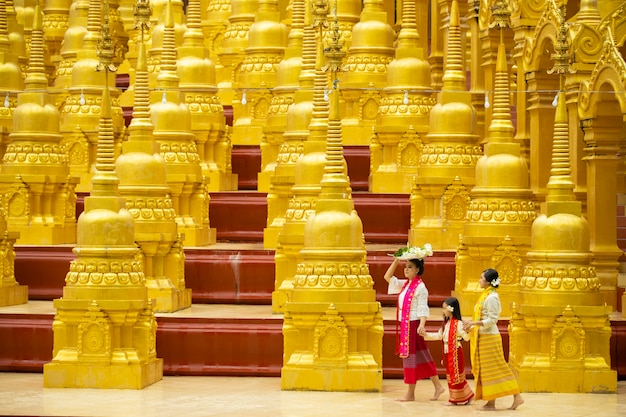 Boeddhisten in lokale culturele kleding reizen om verdienste te verdienen, die onderweg veel gouden pagoden hebben.