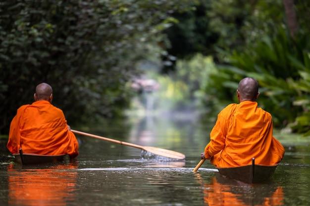 Boeddhistische monnik in kleine houten boot die in kanaal vaart om 's ochtends eten te ontvangen