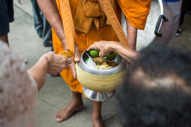 Boeddhistische monniken krijgen voedseloffers van mensen voor het einde van de boeddhistische vastendag