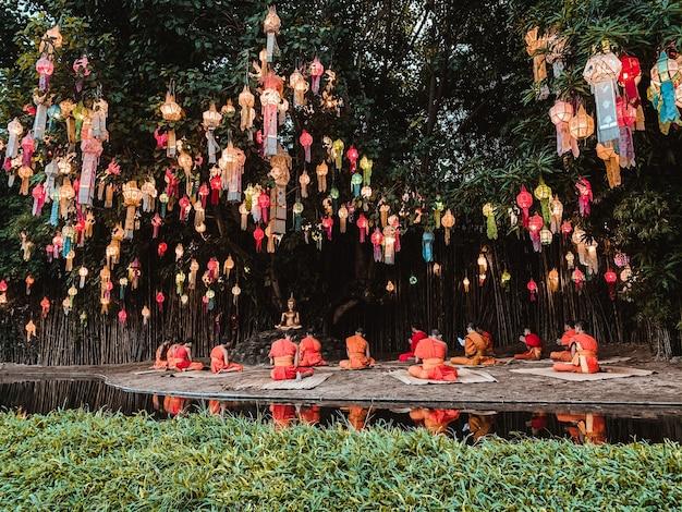 Boeddhistische monniken zitten mediteren onder het licht van de prachtige lantaarn van papier