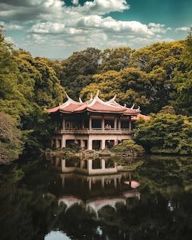 Boeddhistische tempel boven het meer omgeven door bomen, shinjuku gyoen national garden, tokyo
