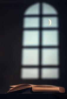 Boek (bijbel, koran) op de tafel tegen de van een groot raam en een halve maan