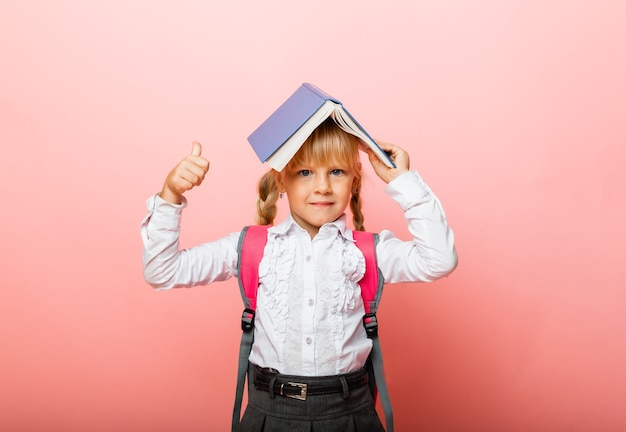 Boek dak boven je hoofd. meisje met een leerboek op haar hoofd. meisje leest een kinderboek op een roze achtergrond.