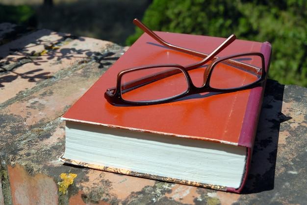 Boek en bril op de muur buitenshuis